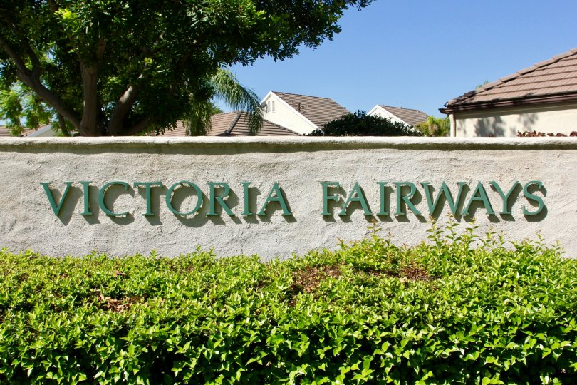 Entrance sign of VIctoria Fairways is among trimmed hedges and large shade trees