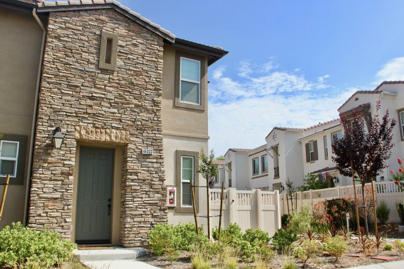 Alegre & Aldea temecula California stone arranged model like walls, linear windows and small grill gates painted white