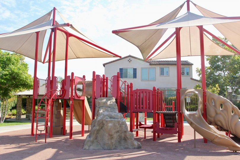 Sails cover the red jungle gym equipment near a townhome in Hawthorne