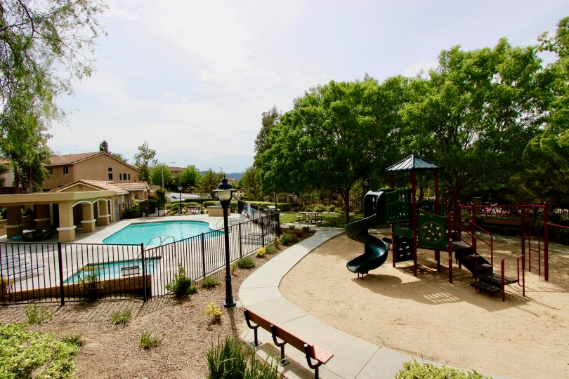 Tree surround a playground, next to the pool and club house at Laurel Creek