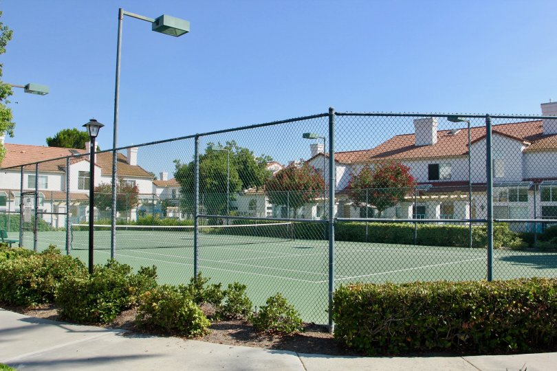 Fenced in tennis court surrounded by white townhomes in Rancho Del Mar
