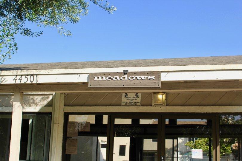 "A sign reading ""Meadows"" sits above an entrance at Rancho Meadows."