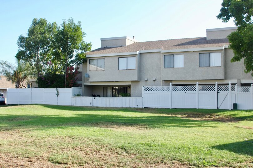 A white fence surrounds a condo building in Rancho Meadows.