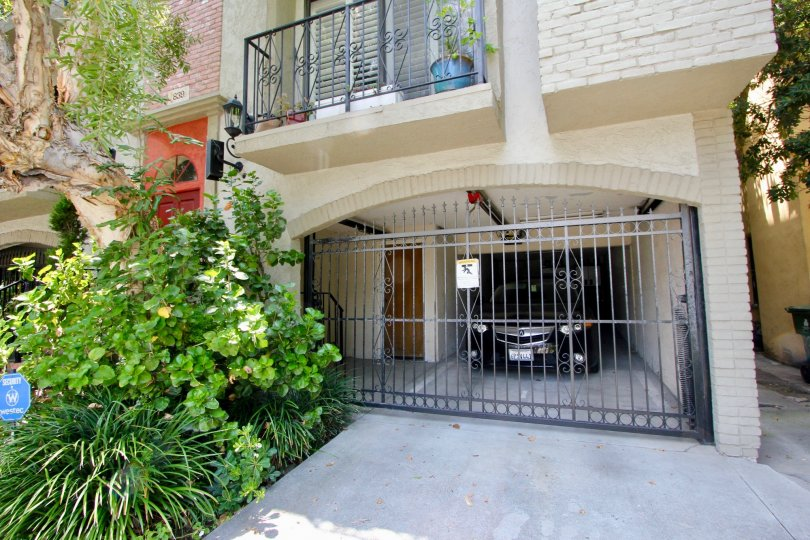 Car parked behind locked gate in a garage attached to a dwelling in Beverly Center, California.