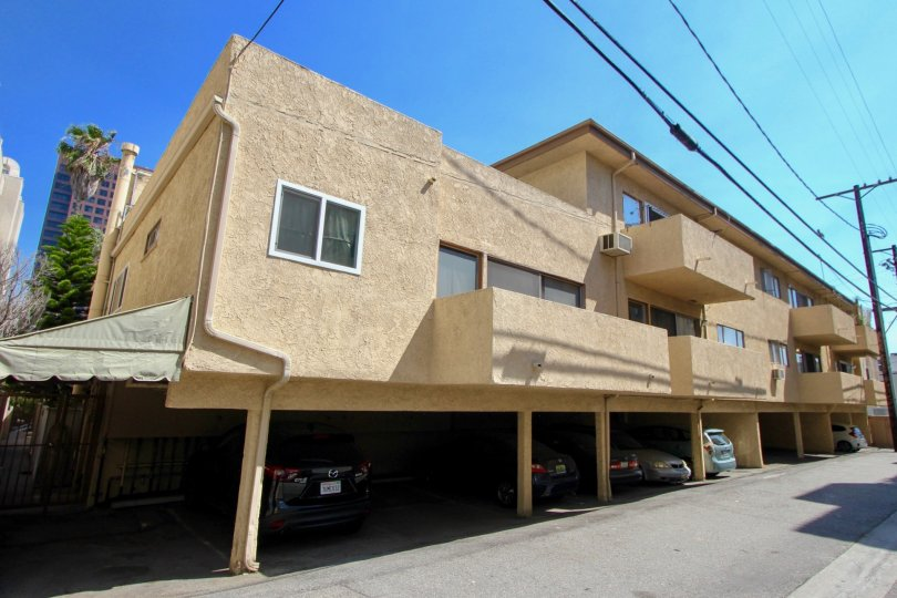 Tan apartment building with spacious parking below in Brentwood, CA