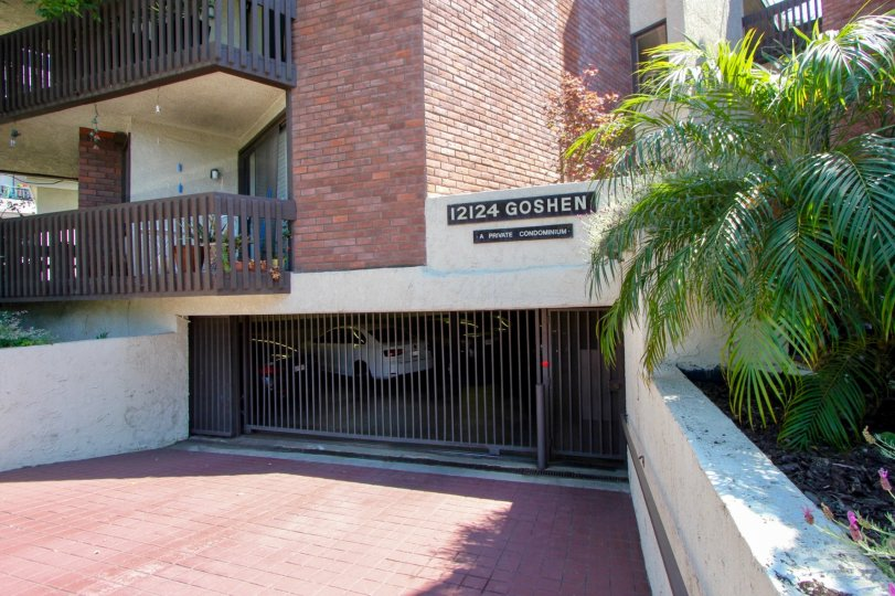 Closed and gated parking garage entrance for an apartment building with balconies visible above and to the left.