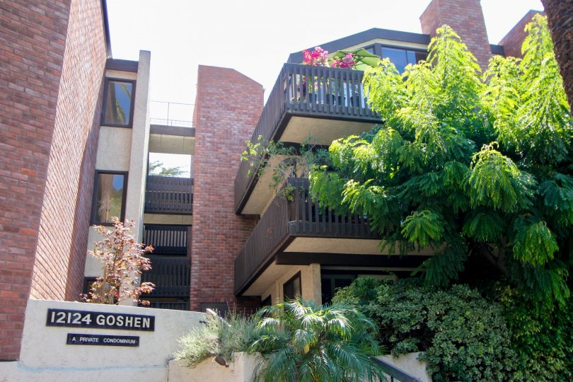 A red brick building at 12124 Goshen with multiple balconies and a large tree