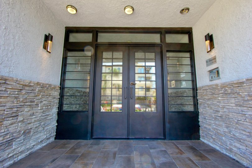 Wooden door entrance with brown tile at the Brentwood Cedar Tree