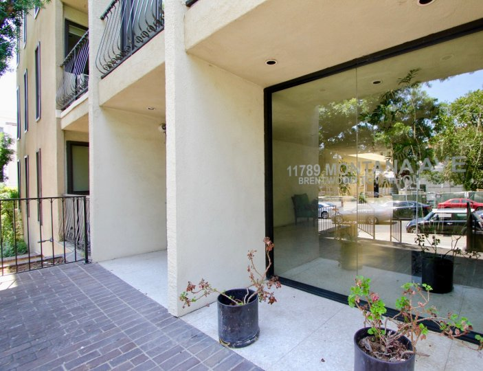 the front part of a building in Brentwood Townhomes, with a big glass view