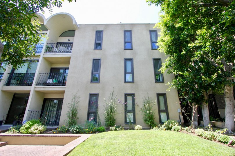 Outside view of three story building with well manicured lawn, lovely flowers and shrubs, and sunny balconies.