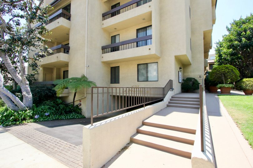 Side of apartment building at Le Provencal with stairs, entrance to parking, and manicured lawn and trees