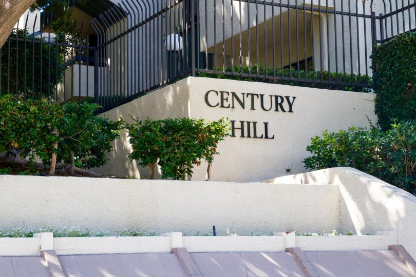 A marquee showing the Century Hill name on a stucco wall new the entrance