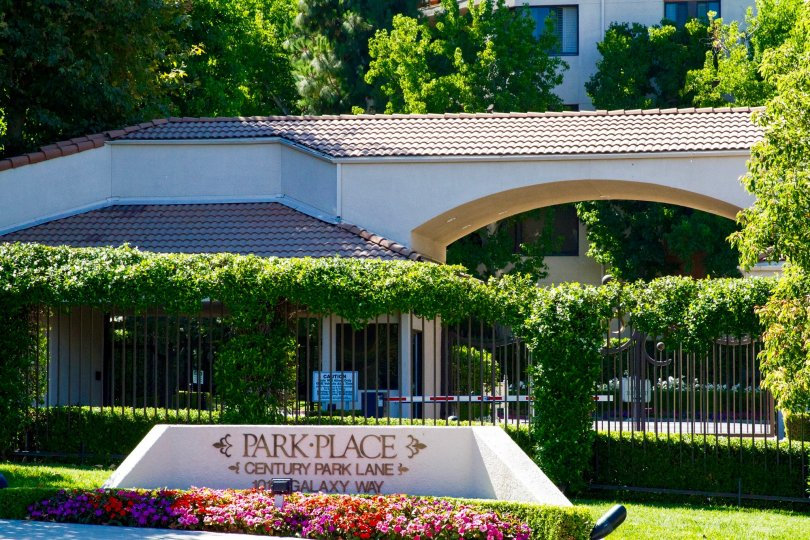 Gold letters on a small stucco structure surrounded by flowers showing Park Place name and address