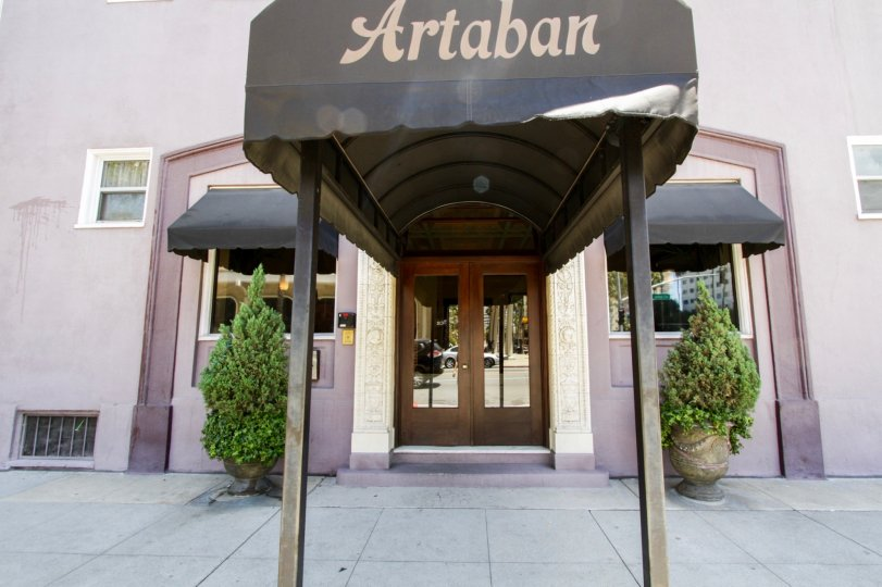 Entry to Artaban two large wood doors with glass insets