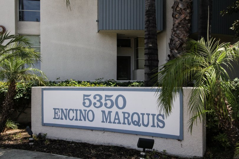The sign showcasing the Encino Marquis building in the background