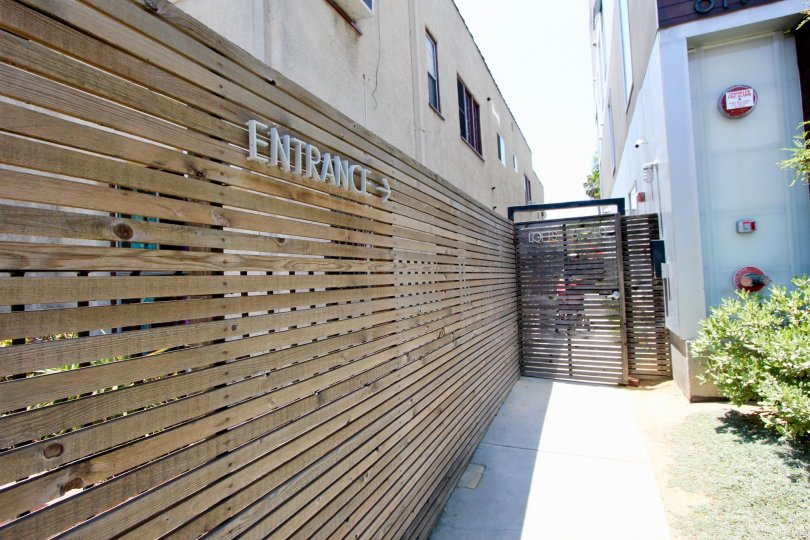 A wooden fence with a sign reading entrance pointing toward a wooden fence in an alley.