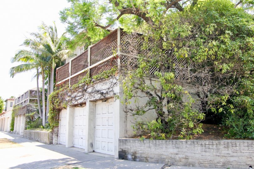 Personal garages at II Borghese with trees and vines, large sidewalk space.