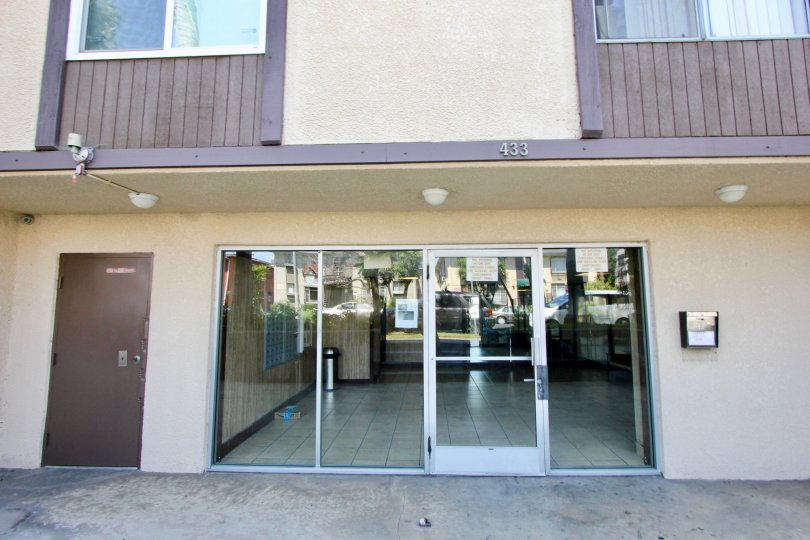 Front entrance at Manhattan Place with large glass windows and door and call box