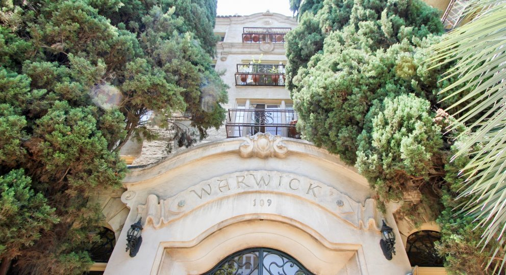 Front entrance at The Warwick. The entrance is arched with several all trees and 3 personal terraces above it.