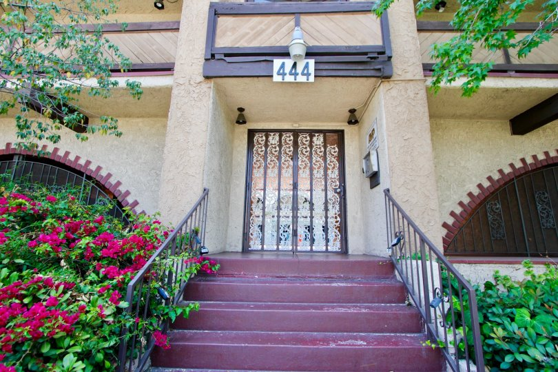 Hancock townhome no. 444 in Koreatown with ornate door and steps, flowers blooming to the left.