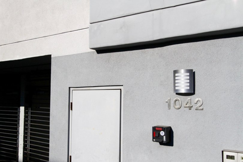 Metal address numbers attached to the stucco side of the Kingsley Manor building