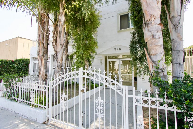 The entrance to building #926 complete with palm trees and a white wrought iron gate in the Manhattan Villa community of Koreatown, California.