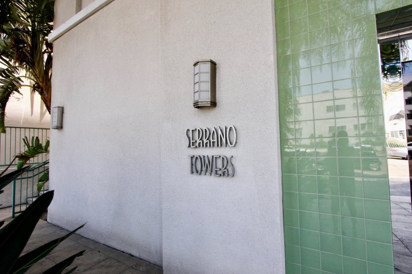 The entrance sign and Serrano Towers building in the shade in Koreatown