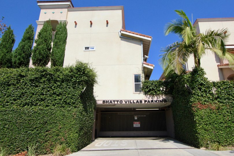 Shatto Villas Parking garage building surrounded by bushes and palm trees.