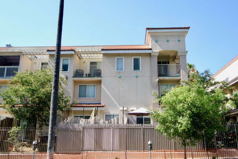 Shatto Villas boasts a gate surrounding the property and three stories of units with balconies.