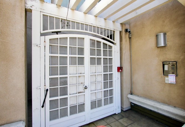 An entrance secure with white screen door, security camera, and call box in the Wilton Plaza community of Koreatown, California.