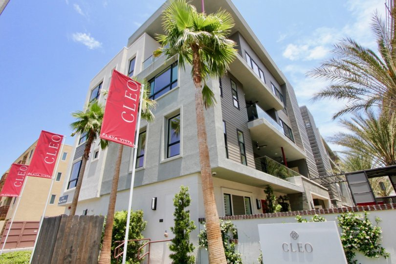 Amazing shot of cleo's entrance signage with red banners beside the beautiful green buildings, playa Vista California