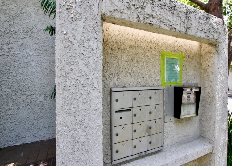 An arrange of mailboxes in the 1037 16th St community with trees and plants in the background.