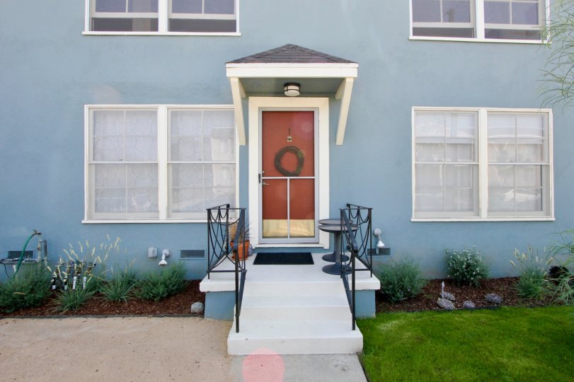 A blue house in the 2314 28th St community with a red front door and white windows
