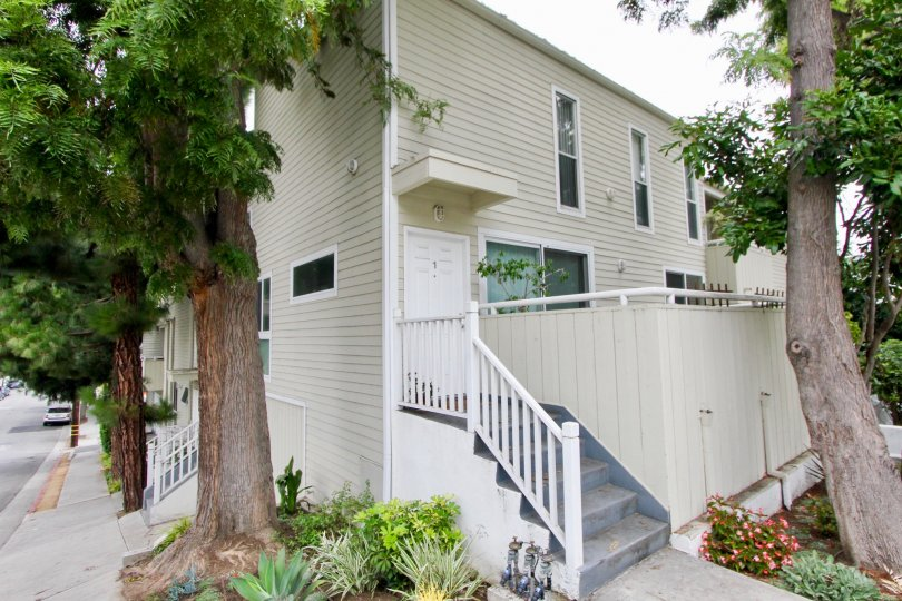 Side view of the house with flowers planted at the entrance and a lush green trees at 3101 Fifth in Santa Monica, California