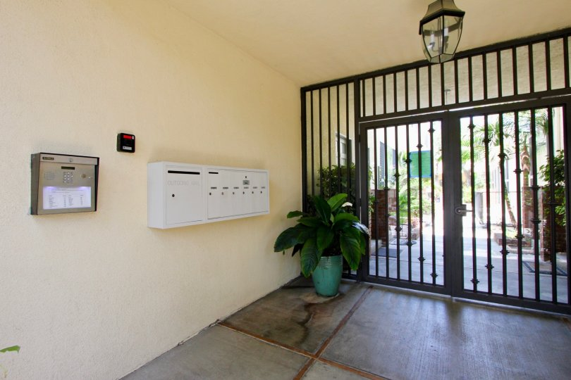Entrance to courtyard secured with double wide iron gate, pleasant light peach color, bank of mail boxes and security intercom, fire alarm and overhead light.