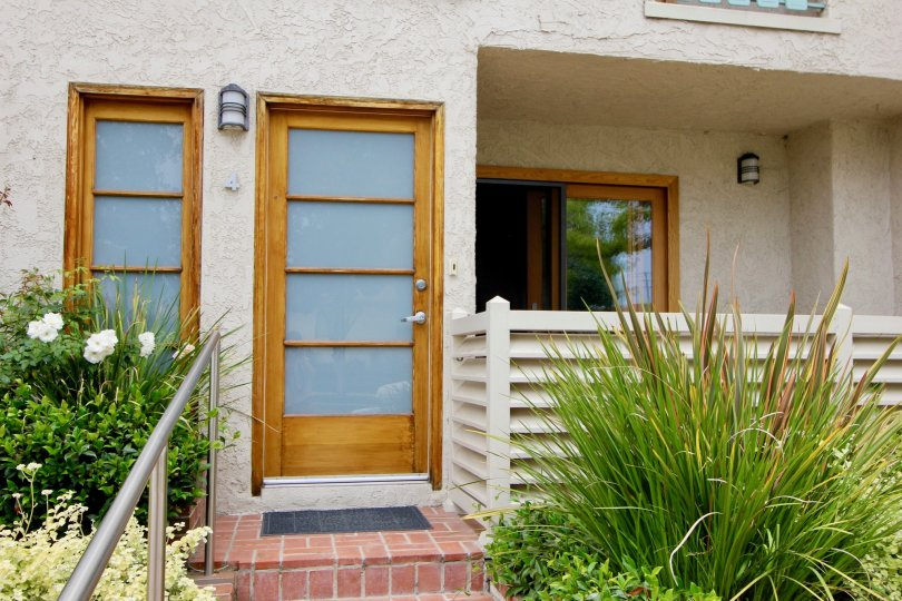 The closed front door of Bay Blue Vista with small plants in front side