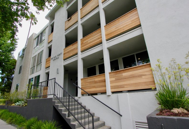 A white building in the Santa Monica Terrace community with wooden balconies
