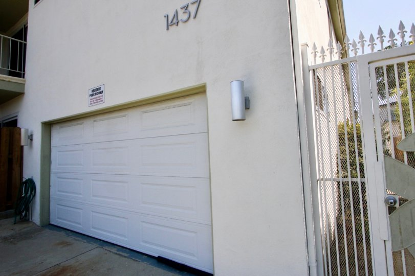 A white house in the Stanford Street Apartments community with a single white garage door