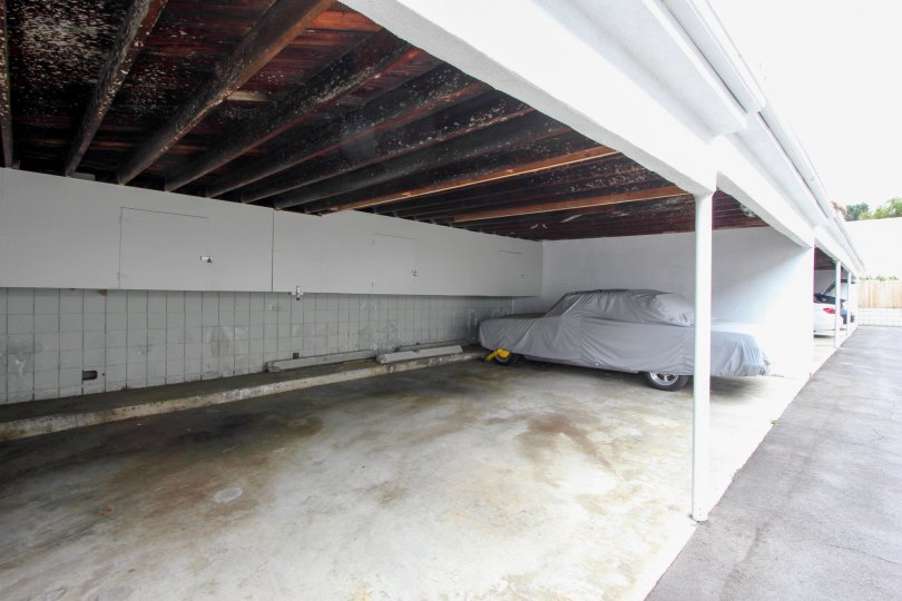 A car in a carport covered by a tarp on Strand IV Santa Monica California