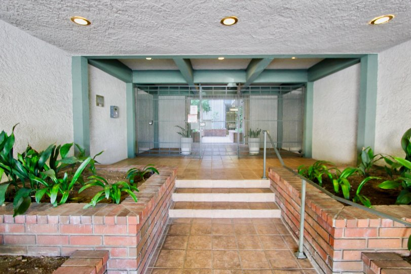 Villa Centinela ceramic and stucco entry with green painted beams and columns in Santa Monica California