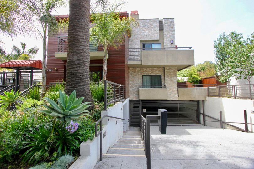 Multi-story building with balconies and garage with palm trees and landscaping