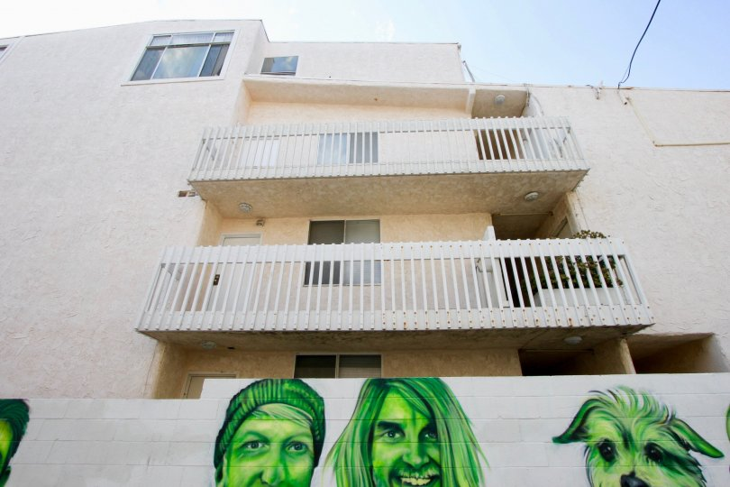 Green portraits below white balconies on a sunny day at the Navy Estates