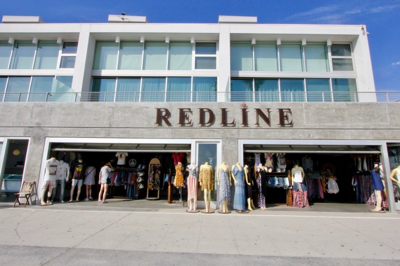 Large bay window apartments located above a retail clothing store Redline. The apartments have balconies that overlook the store.