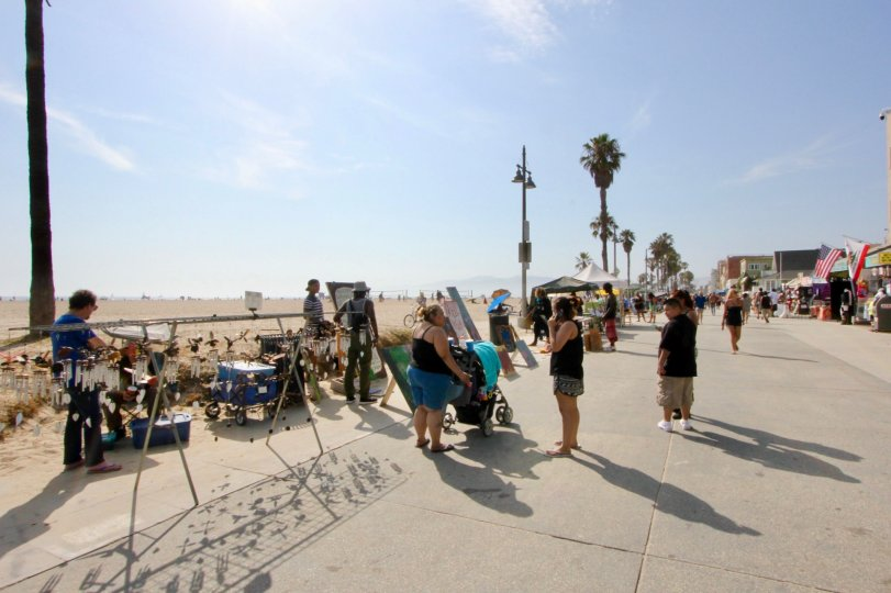 A sunny day at Thornton Lofts in Venice, CA on the boardwalk with a beach and tourists