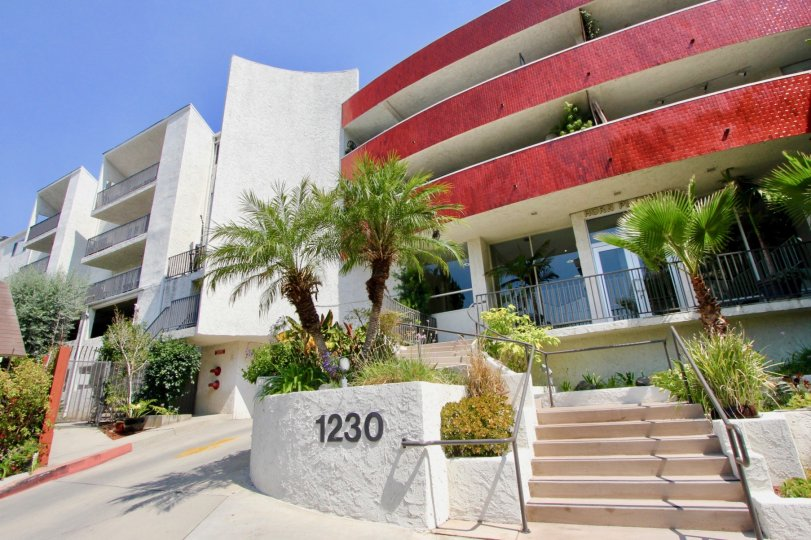 1230 Horn Plaza and her white and red walls with surrounding green plants, West Hollywood, California