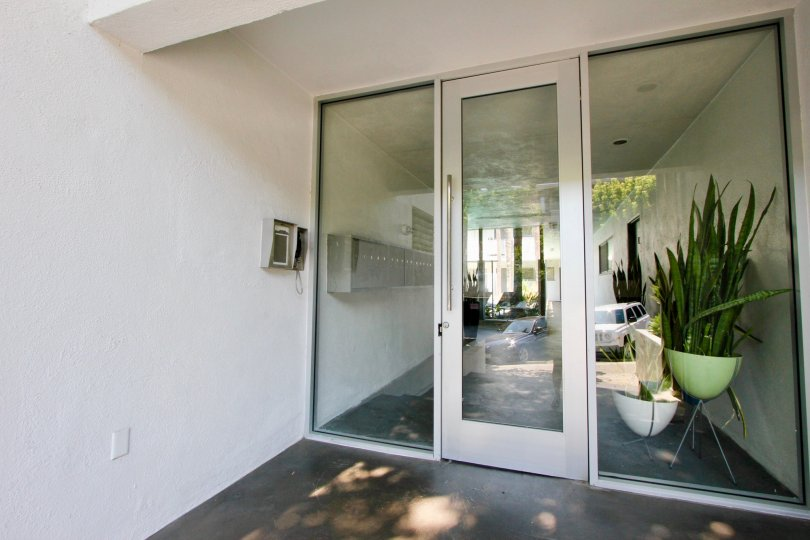 Glass door entranceway with secure intercom and keypad entry. The door leads to a foyer with mailboxes along the wall and potted plants along the opposite wall Reflection suggest the entrance faces a parking area