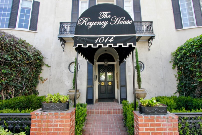 A street view of The Regency House, a building with a garden lined walkway and awning.
