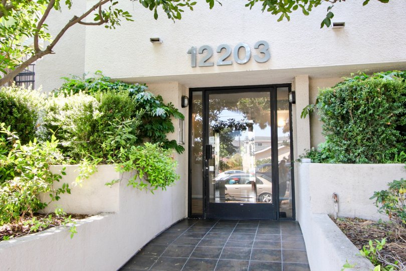 12203 Idaho, west la, California is A beautiful entrance with pretty good gate and lots of greenery including plants and trees. Colourfull flowers are adding life in the picture.