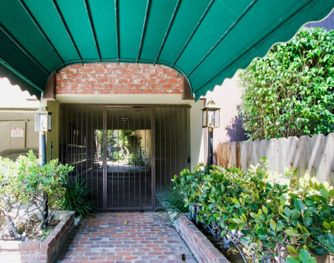 The gated entrance to a building, underneath a green awning in the 1722 Brockton community in West LA, California