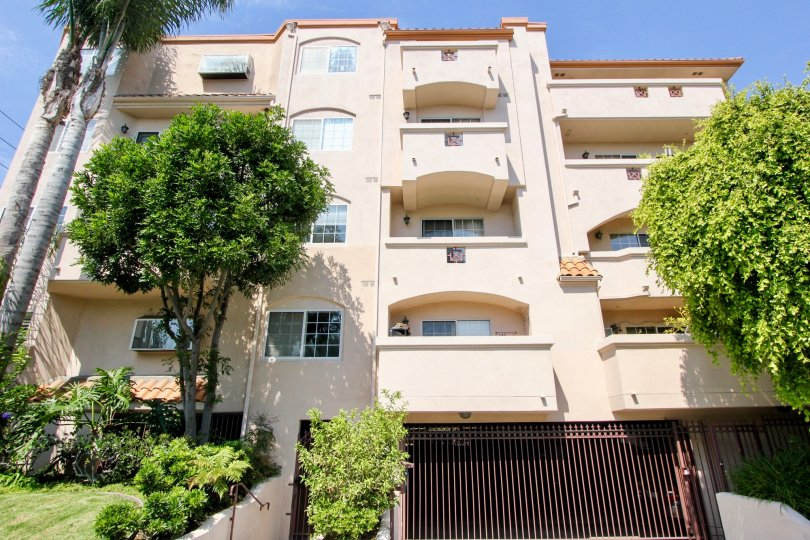 A 3 floors apartment complex with a parking entrance has palm trees around and tiles and spanish details